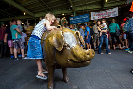 SEATTLE - JULY 5: Pike Place Markets unofficial mascot, Rachel on July 5, 2014 A bronze cast piggy bank that weighs 550 pounds, has been located since 1986 at the corner of Pike Place Market.