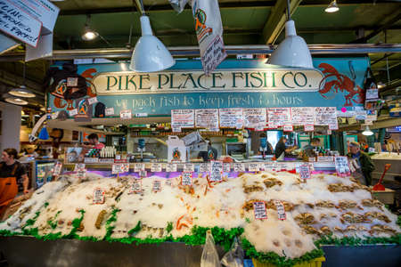 pike place market: SEATTLE  JULY 5: Customers at Pike Place Fish Company wait to order fish at the famous seafood market on July 5, 2014. This market, opened in 1930, is known for their open air fish market style.