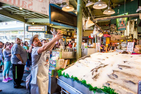 SEATTLE  JULY 5: Customers at Pike Place Fish Company wait to order fish at the famous seafood market on July 5, 2014. This market, opened in 1930, is known for their open air fish market style.