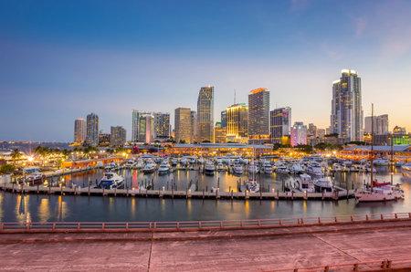 Miami city skyline panorama at twilight with urban skyscrapers, marina and bridge