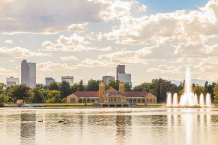 denver skyline with mountains: Scenic of Denver Colorado skyline, with Rocky Mountains in the background and City Park Lake in the foreground. Stock Photo