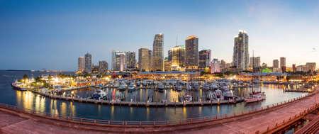 Miami city skyline panorama at twilight with urban skyscrapers, marina and bridge photo