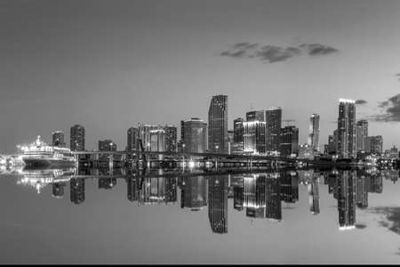 Miami city skyline panorama at twilight with urban skyscrapers and bridge, black, white