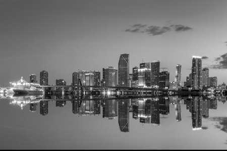 night views: Miami city skyline panorama at twilight with urban skyscrapers and bridge, black, white