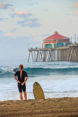 huntington beach: The Huntington Beach pier at sunrise, CA with surfer