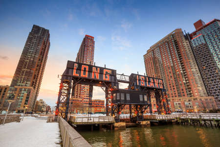 long island: the buildings of long island in front of east river at twilight