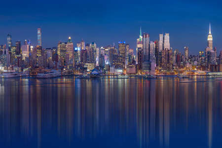 hudson: New York City with skyscrapers illuminated over Hudson River panorama