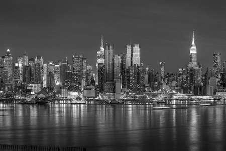New York City met wolkenkrabbers verlicht over Hudson Rivier panorama in zwart-wit