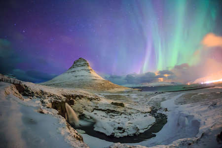 Spectacular northern lights appear over Mount Kirkjufell and waterfall in Iceland. Фото со стока
