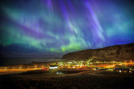 auroral: Auroral KP9 display over Vik city in Iceland. Stock Photo