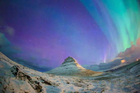 Spectacular northern lights appear over Mount Kirkjufell and waterfall in Iceland. Reklamní fotografie