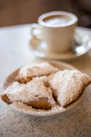 powdered sugar: Beignets (French style donuts) topped with sugar and a cup of coffee in the background Stock Photo
