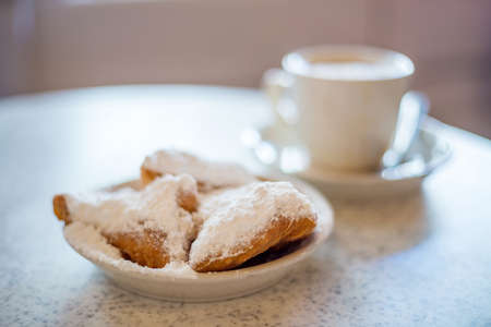 Beignets (French style donuts) topped with sugar and a cup of coffee in the background Фото со стока