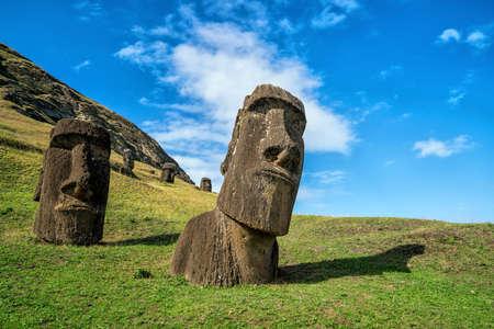 moai: Moais en el volcán Rano Raraku en la isla de Pascua, Chile con el cielo azul