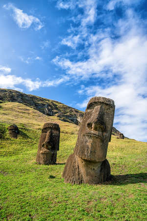 Moai statues in the Rano Raraku Volcano in Easter Island, Chile with blue sky
