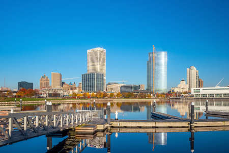 Milwaukee skyline  with city reflection in lake Michigan and harbor pier.