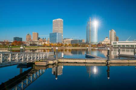 Milwaukee: Milwaukee skyline  with city reflection in lake Michigan and harbor pier.
