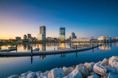 waterfront property: Milwaukee skyline at twilight with city reflection in lake Michigan and harbor pier.