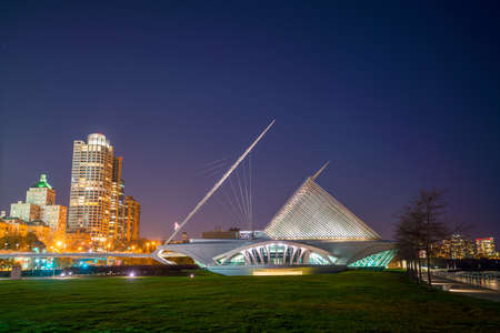 Milwaukee skyline at twilight with city reflection in lake Michigan and harbor pier.