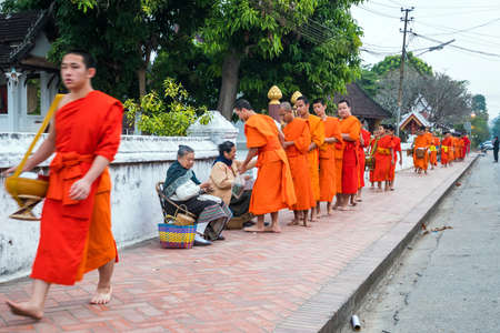 LUANG PRABANG, LAOS - FEB 10: Buddhist monks collecting alms in the morning. The tradition of giving alms to monks in Luang Prabang has been extended to tourists on Febuary 10, 2017
