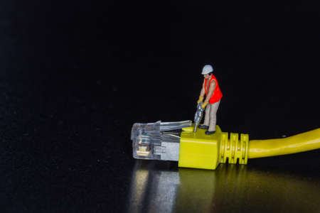 Miniature worker using a hammer drill on a yellow network Stock Photo