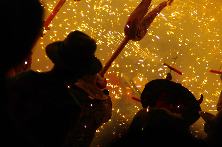 Men disguised as masked devil, with symbology and fireworks in traditional festival Foto de archivo