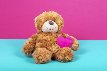 Teddy bear with felt heart on two color background Stock Photo