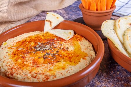 Plate of hummus with hindu bread and crudites of carrot and pepper. Vegan and vegetarian food Standard-Bild