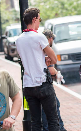 Charlottesville, Virginia USA August 12, 2017 Redneck Revolt member armed with handgun helps keep Justice park secure staging area for activists protesting UTR rally supporting confederate statue Editöryel