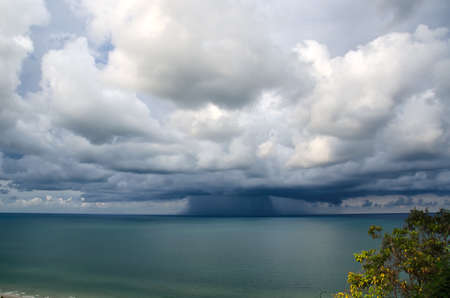 strom: Sandy beach and green sea over of it is a cloudy strom Stock Photo