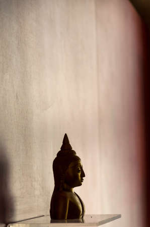 reflex: Head of Buddha on the stand reflex the shadow to the wall