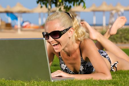 Photo beautiful girl on the beach with laptop. Rests on the grass. Sincerely happiness. photo