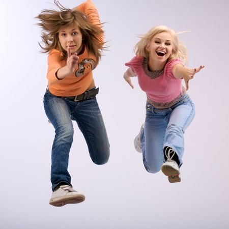 Two young women and happy smiling facial expression jumping long.