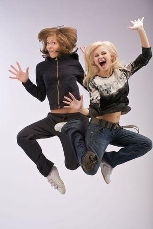 Dancing due donne sorridente e felice espressione facciale salto.
