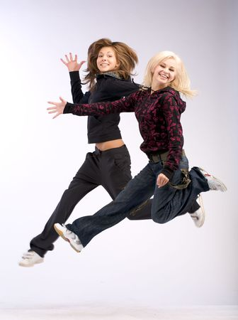 synchronously: Jump of two women with long hair