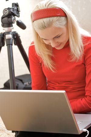 aficionado: Mujer joven fot�grafo con un ordenador port�til y mecanismos para tomar fotos.
