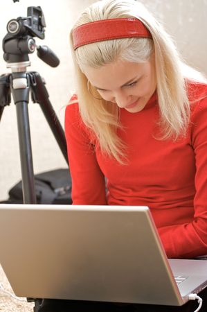 Young Female Photographer with a laptop and gear for taking photos.
