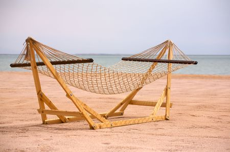 vacationing: A view of a wooden framed hammock on a beach at the Red Sea on a summer day. Stock Photo