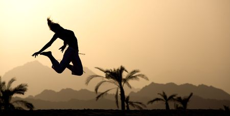 Young woman at sunset jumping up on a mountains and tropical landscape background.  Excellent image for your banners on summer tourism. Stock Photo - 3150183