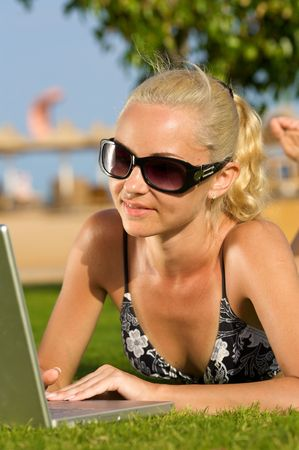 Portrait of a young woman with laptop on the beach.  photo