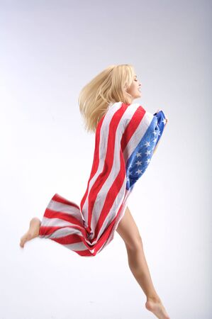 Running woman in American flag with blonde long hair. Stock Photo