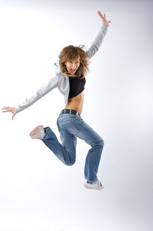 Dancing woman with brown long hair and happy smiling facial expression jumping up. Stock Photo