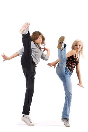 A studio view of two pretty young women dancers in casual clothes in a high kicking pose.