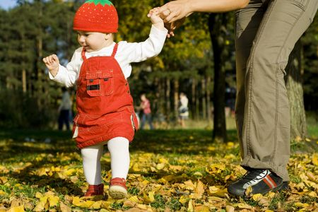 Photograph of the first  step on the grass, with the support of the autumn mother. outdoor snapshot. Stock Photo