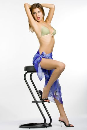 The very sexual naked girl in a sitting on a high chair. A white background. Stock Photo
