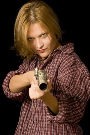 A young woman with a vintage gun in her hand, aiming at the camera. Black background. photo