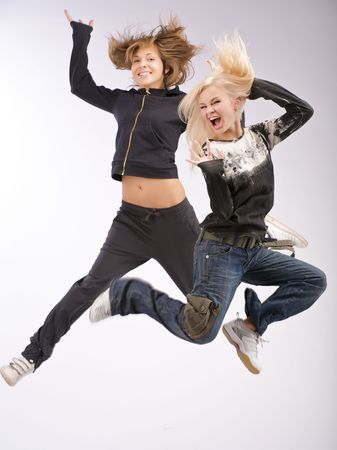 Jumping emotional women. The blonde and the brunette. Stock Photo