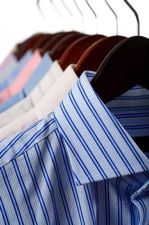 ropa colgada: Close-up rack camisas aisladas sobre fondo blanco