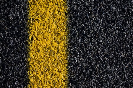 A closeup view of the yellow marking on a asphalt road. photo