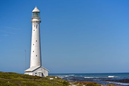 A tall white lighthouse facing the Indian Ocean, on a South African beach. Stock Photo